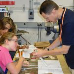 Instructor helping student duing model workshop
