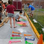 High school students spray painting model rockets